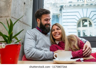 Young couple in love sitting on the bar with coffee and talking