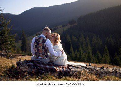Young couple in love sitting on the wood log with their backs turned to the camera, hugging each other in the mountains