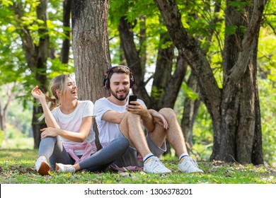 Young couple in love sitting on grass in park with legs crossed while using cell phone and music in black headphones, lifestyle concept