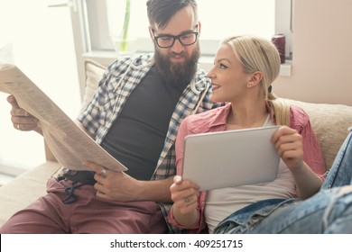 Young couple in love sitting on a couch in their apartment next to the window, enjoying their free time, reading newspaper and surfing the web on a tablet computer. Lens flare effect on window