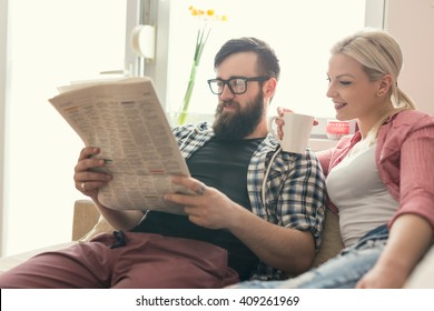 Young couple in love sitting on a couch in their apartment next to the window, enjoying their free time, reading newspaper and drinking coffee. Lens flare effect on window