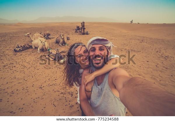 Joven pareja enamorada parada cerca de muchos camellos en el desierto de África tomando fotos con ellos, disfrutando del desierto del safari