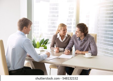 Young couple in love starting family life, applying for mortgage to buy accommodation, purchasing, renting new apartment, meeting with real estate agent, signing loan contract, choosing place to live