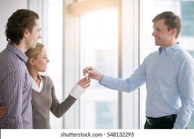 Young couple in love starting family life, got a chance of acquiring independent home ownership, given key from new apartment, social renting, purchasing new apartment, meeting with real estate agent