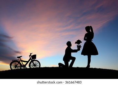 Young couple in love at sunset background.