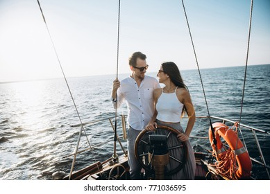 A young couple in love swims on a luxury yacht, they stand at the helm looking at each other and smiling