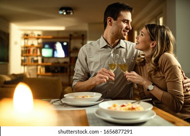 Young couple in love toasting with Champagne while sitting close to each other at dining table.