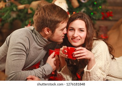 Young couple in love together in a warm cozy home with a cup of coffee in winter