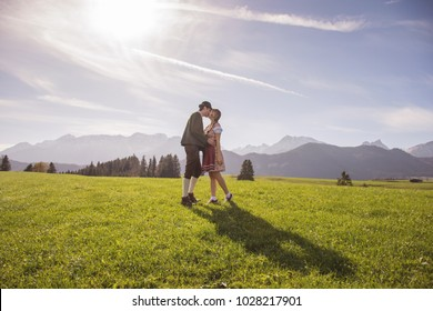 Young couple in love with traditional german clothes kissing in beautiful rustic panorama with mountains from Allgau, Bavaria. Lovers in traditional costumes. Girl in beautiful dirndl dress