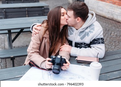 Young couple in love travels and kissing outdoor in cold winter weather