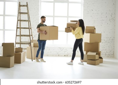Young couple in love unpacking cardboard boxes just moved to rent apartment making renovation,casually dressed male and female colleagues carrying stuff for delivery service relocating in new office