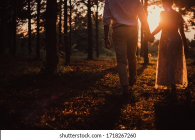 Young couple in love walking and holding hand on beautiful sunset background. Pine forest