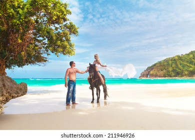 Young couple in love walking with the horse on a tropical beach. Tropical sea in the background. Summer vacation.