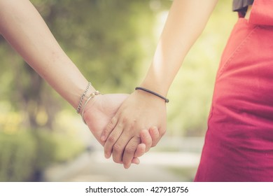 Young couple in love walking in the park holding hands , selective focus , copy space