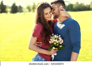 Young couple in love walking in the park holding flowers