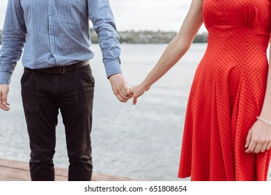 Young couple in love walking in the summer park holding hands looking in the sunset