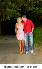 young couple in love walking through wood