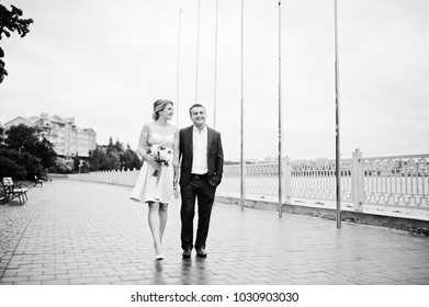 Young couple in love walking the waterfront. Girl with bouquet.