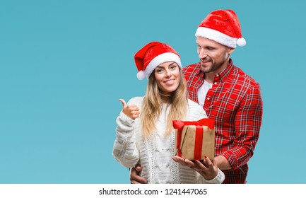 Young couple in love wearing christmas hat and holding present over isolated background pointing and showing with thumb up to the side with happy face smiling