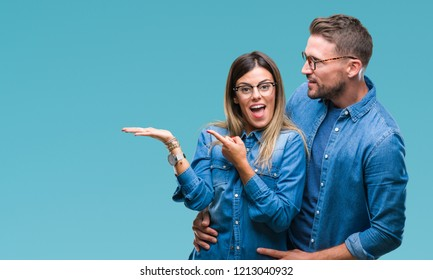 Young couple in love wearing glasses over isolated background amazed and smiling to the camera while presenting with hand and pointing with finger.