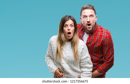 Young couple in love wearing winter sweater over isolated background afraid and shocked with surprise expression, fear and excited face.