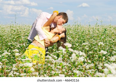 Young couple in love who kissing at the meadow