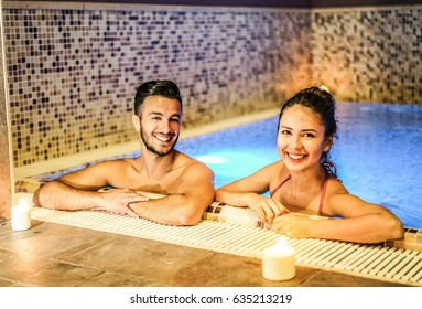 Young couple of lovers enjoying spa swimming pool  - Romantic love story inside resort hotel - Relationship concept with boyfriend and girlfriend in holidays - Soft focus on woman face - Warm filter