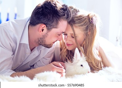 The young couple of lovers and a white decorative rabbit celebrates St. Valentine's Day