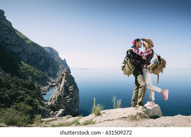 Young couple of loving Backpackers in the mountains kissing on a cliff sea. Romantic adventures man embracing a woman outdoors. Hikers.