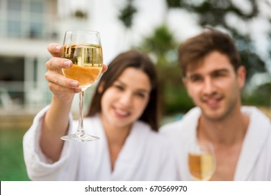 Young couple  in a luxury hotel tasting a glass of white wine