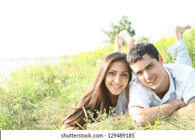 Young couple lying around in the nature on green grass background