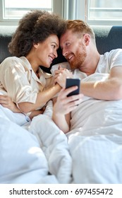 Young couple lying in the bed, he is holding mobile phone