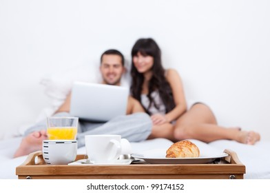 Young couple lying up in bed with laptop and breakfast tray in foreground