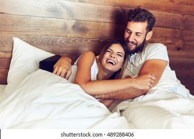 jovem casal deitado no cama e rindo enquanto cócegas cada outros