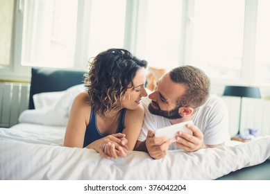 Young couple lying In bed, looking into mobile phone