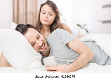 A young couple lying in bed. One of them use the phone and flirting. The other person is jealous and spies of the arm. The concept of jealousy and distrust.