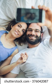 Young couple lying In bed, taking selfie