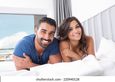 Young couple lying in bed wearing pajamas