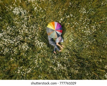 Young couple lying down in the middle of a meadow and hiding behind umbrella (drone photo).