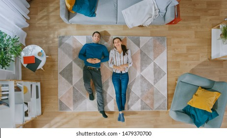 Young Couple is Lying Down on the Floor and Talking. They Point Fingers at the Ceiling. Cozy Living Room with Modern Interior with Carpet, Chair, Table, Book Shelf, Plants and Wooden Floor. Top View.
