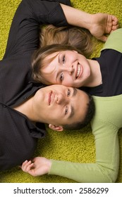 young couple lying head next to head on the green carpet
