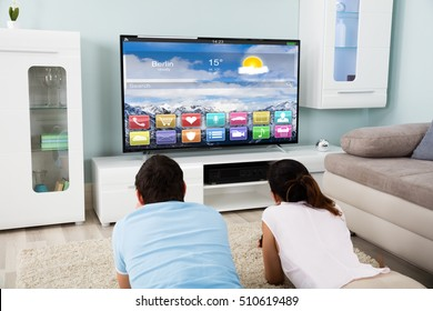 Young Couple Lying On Carpet Watching Television Showing Colorful Application