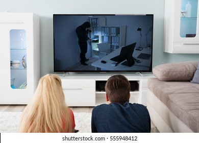 Young Couple Lying On Carpet Watching Suspense Movie On Television At Home