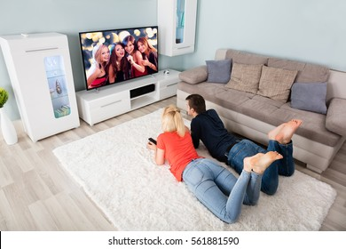 Young Couple Lying On Carpet Watching Television At Home