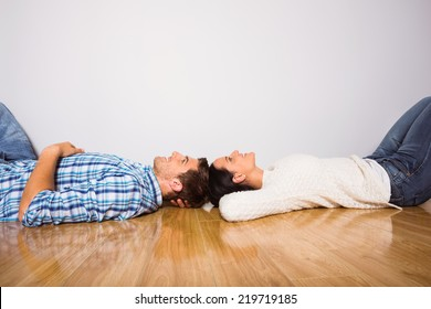 Young couple lying on floor smiling at home