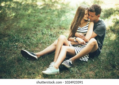 Young couple lying on the grass on sunny day, embracing,
