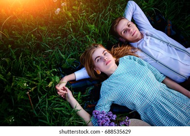 young couple lying on the grass and relax, view from above.