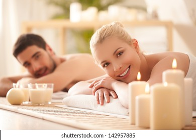 Young couple lying on the massage table and smiling.