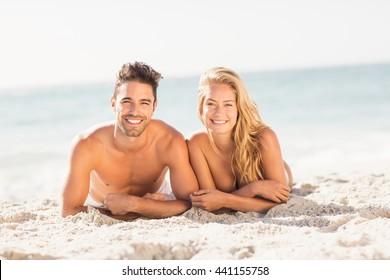 Young couple lying on sand on the beach