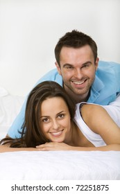Young couple lying on a white sofa embracing and smiling